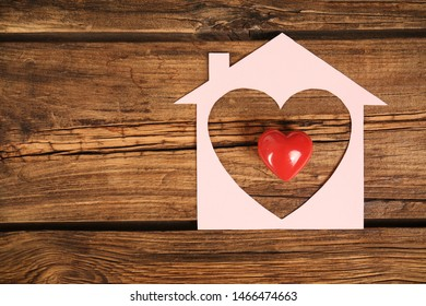 Paper house and red heart on wooden background, flat lay. Space for text