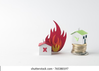 A paper house that burns and a safe house over a coin pile: fire insurance concept