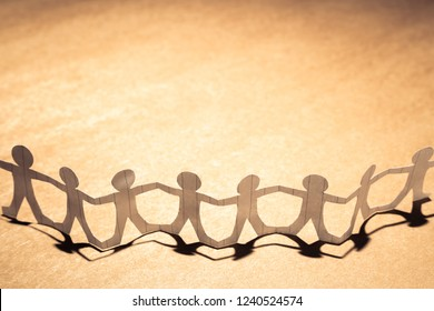 Paper human chain on brown paper