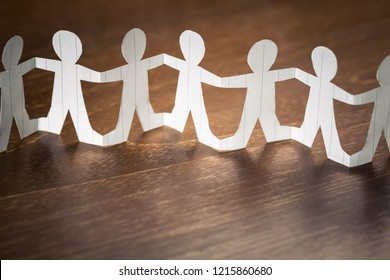 Paper human chain on wood table