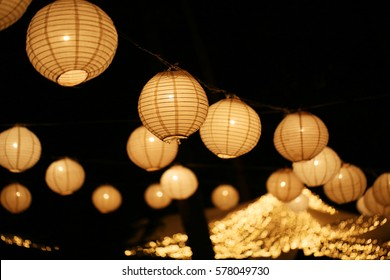 a paper lantern floats on a dark back ground on wedding day