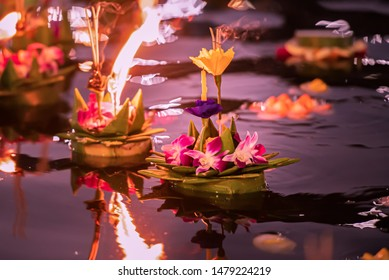 Paper lotus flower with candle floating on a river at night in Loy krathong festival, traditional Siamese new year festival celebrated in Thailand.