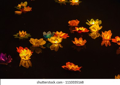 Paper lotus flowers with candles float on a river at night to mark the Chinese Mid-Autumn Festival
