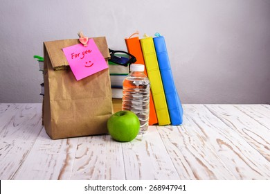 paper  lunch bag  with apple,water and books  on desk with post-it note,