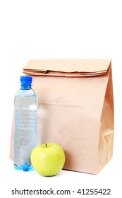 paper lunch bag with fresh apple and water on white - food and drink