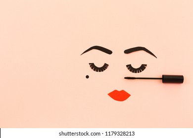 Paper made woman face with make up. Red lips, bold eye brows, long lashes and beauty spot. Copy space for your text. Top view, flat lay. Pastel pink background.