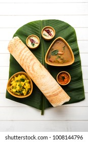 Paper Masala dosa is a South Indian meal served with sambhar and coconut chutney over fresh banana leaf. Selective focus
