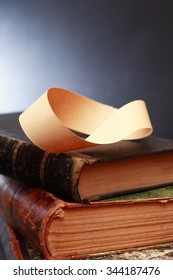 Paper Mobius strip on old books against dark background