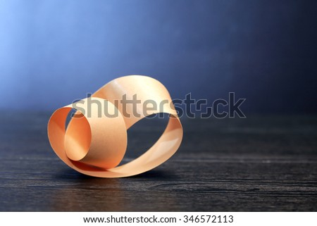 Paper Mobius strip on wooden board against dark background