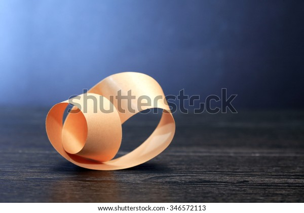 Paper Mobius strip on wooden board against dark background