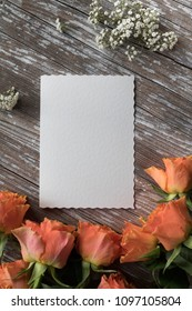 paper mockup with roses and baby breath flowers on wooden background