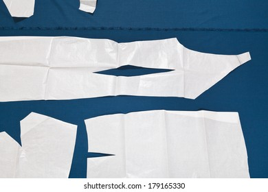 paper model of dress on blue fabric for dress cutting