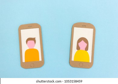 Paper models of two mobile phones with user profile images on screen displays