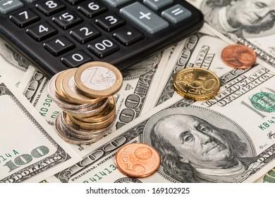Paper money, coins and calculator - closeup shot