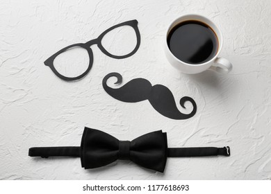 Paper mustache, glasses, bow tie and cup of coffee on white textured background. Father's Day celebration