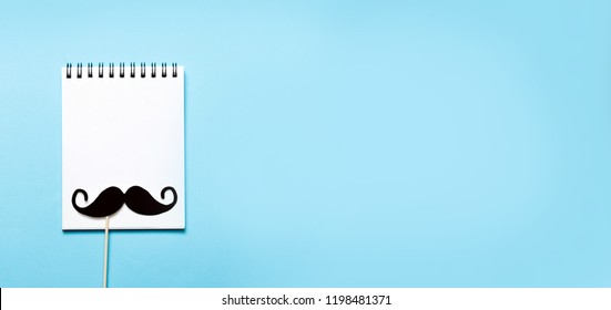 paper mustaches and a notepad on blue background. November concept, flat lay, top view, copyspace for text.