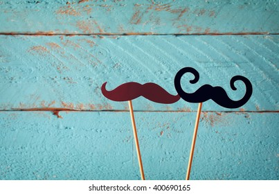 paper mustaches in sticks in front of wooden background. vintage filtered image