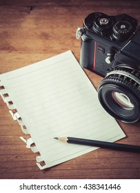 paper note book and pencil with old camera on wooden background