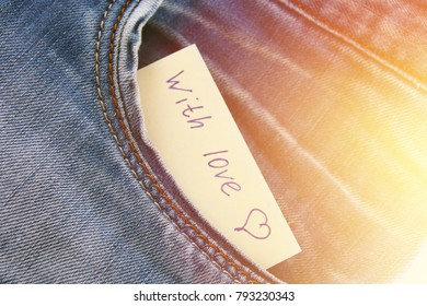 Paper note with the inscription I love you, with love peeps out of the pocket of jeans trousers. The concept of the day of lovers. St. Valentine's Day