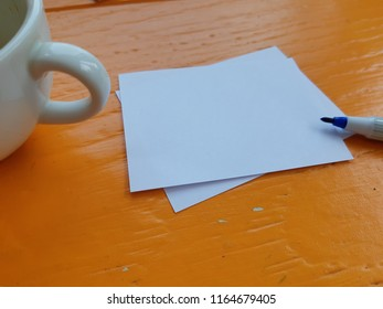 paper note with pen and a cup coffee on table