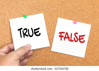paper note with text ( true or false ) pin on corkboard  with hand holding , decision concept