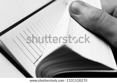 Paper notebook in hand, pages and fingers