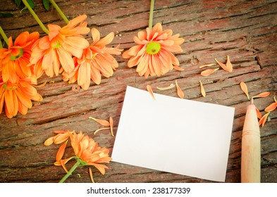 Paper, notebooks, pens with orange flowers on the table, vintage retro style.