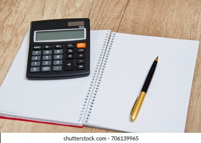 Paper notepad, calculator and pen on wooden desk