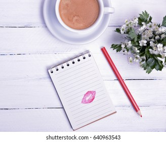 Paper notepad with a trace of a kiss from red lipstick, next cup of black coffee, empty space on the left