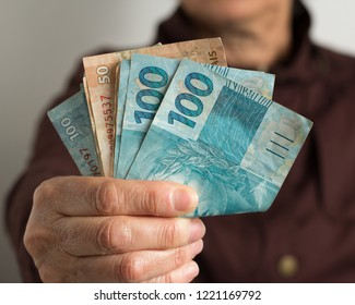 Paper notes from Brazil. Brazilian cash. Front view senior person holding bills.