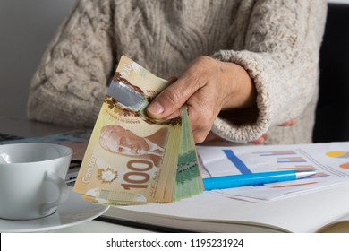 Paper notes from Canada. Dollar. Canadian cash. Person giving papernotes on desk.