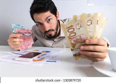Paper notes from Canada. Dollar. Canadian cash. Young adult holding many bills on table.
