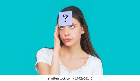Paper notes with question marks. Doubtful girl asking questions to himself. Confused female thinking with question mark on sticky note on forehead. Thinking woman with question mark looking up.