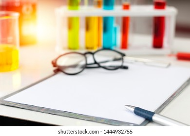 Paper on clipboard with pen for recode chemical test report with test tubes and equipment technical background. Chemical liquid in Laboratory with samples in test tubes.