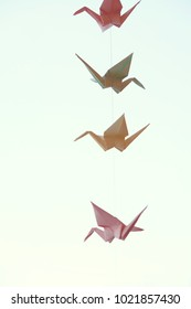 paper origami cranes. garland of origami birds hanging on  natural background. soft selective focus.