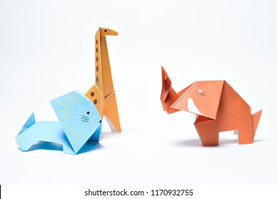 Paper origami giraffe, lion and elephant on white background