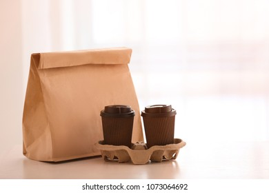 9e0eff3990b Paper package and coffee cups on table against light background. Food  delivery