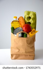 Paper package with various food, oil, bread, eggs, tomato, cucumber, can, spaghetti. Delivery service or charity concept.