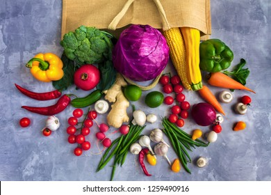 Paper package of vegan vegetarian with fresh colorful tasty raw organic raw healthy food vegetables and fruits: cabbage, brocolli, pepper, carrot, tomato, champignon, chili isolated on grey background
