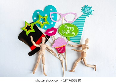 paper party accessories and two wooden mannequins on white background