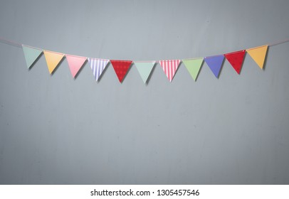 Paper party flags for decoration and covering on grey concrete textured copy space background