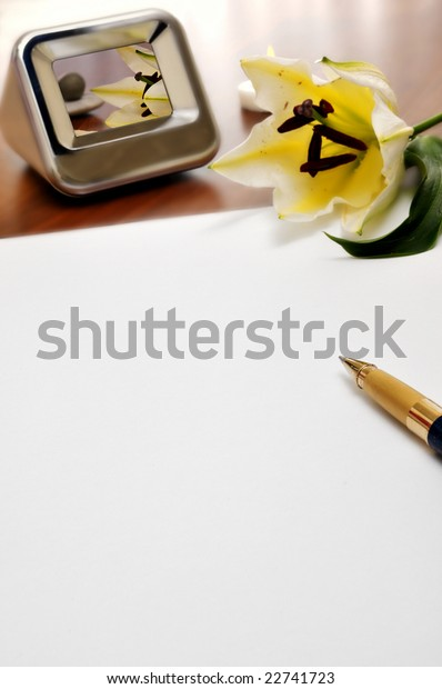 paper, pen, flower and a photo frame on a table