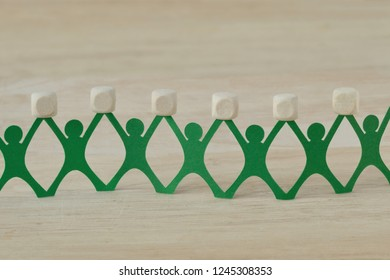 Paper people chain holding blank wooden cubes