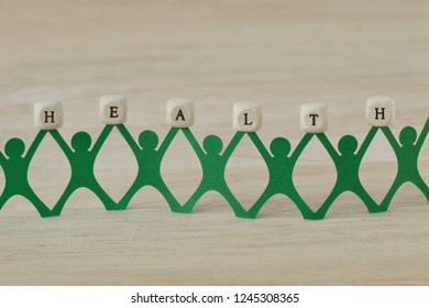 Paper people chain holding Health text written on wooden cubes