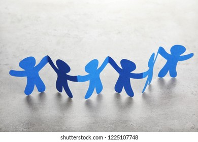 Paper people chain on light background. Helping and supporting concept
