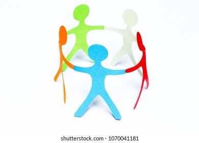 Paper people of different colors standing in a cycle holding hands. Concept of teamwork, diversity and friendship. Isolated on white background.