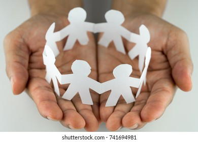 Paper people in the hands. Concept of insurance, social protection and support.