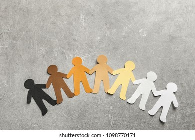 Paper people holding hands on grey background, top view. Unity concept