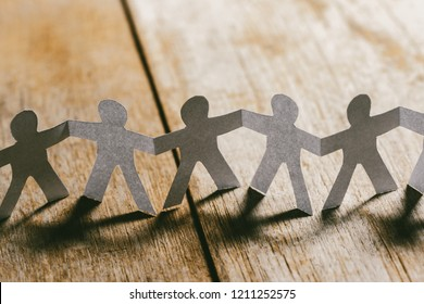 Paper People Holding Hands on a wooden table