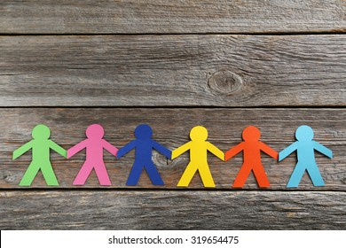 Paper people on the grey wooden background